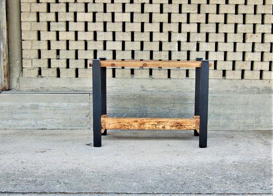 Hochtisch aus Stahl und Altholz vor einer Mauer