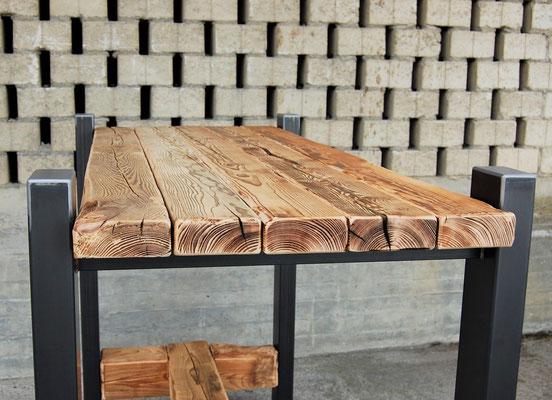Tisch aus Altholz mit Stahlbeinen vor einer Mauer