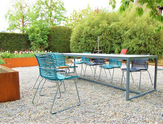 Gartentisch mit blauen Stühlen, in einem blühendem Garten