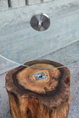 Geschraubte Verbindung von einer runden Glasplatte mit einem Baumstamm