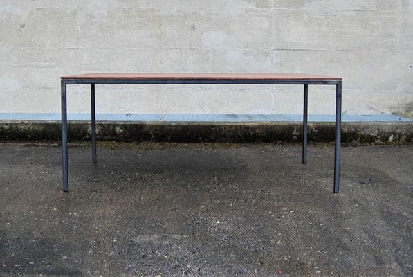 Seitenansicht von einem Tisch vor einer Betonwand bei nassem Boden