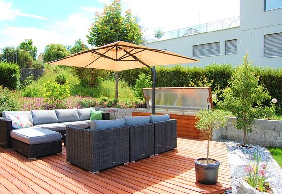 Garten-Lounge mit Sonnenschirm und Kissenbox mit geöffnetem Deckel