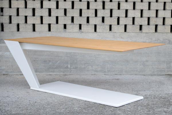 Tisch mit Stahl-Untergestell vor einer gemauerten Wand