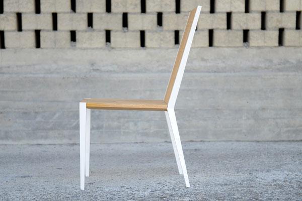 Seitenansicht von einem Stuhl aus Holz vor einer gemauerten Wand