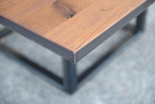 Detailaufnahme von einem Quadratischen Tisch mit einem Winkelrahmen aus Stahl der das Tischplatte einrahmt