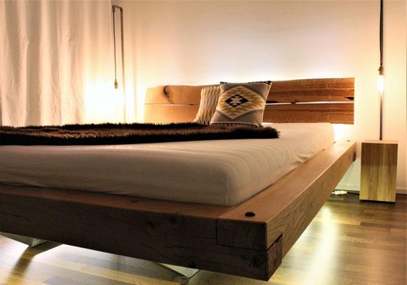 Holz-Bett in einem Zimmer mit Holzboden und zwei Lampen