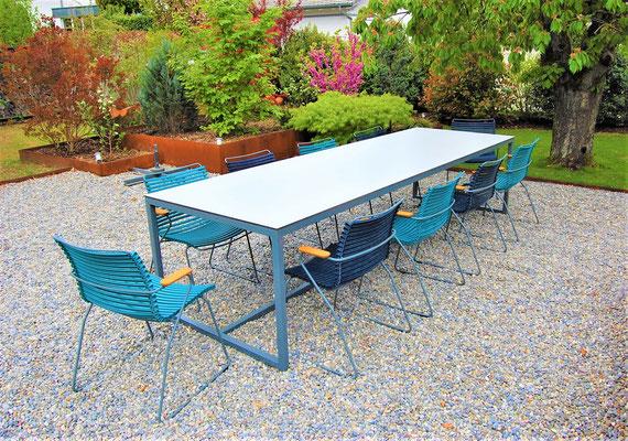 Gartentisch  mit 10 Stühlen auf Kies in einem Garten