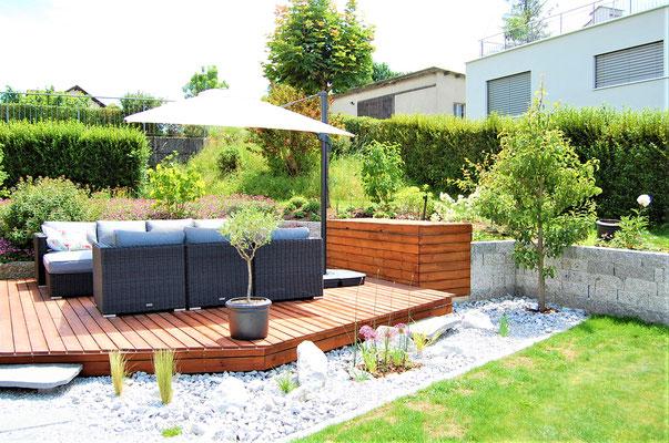 Garten-Lounge mit Sonnenschirm und Kissenbox mit geschlossenem Deckel