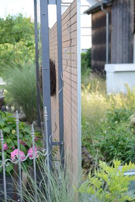 Sichtschutz-Wand aus Holz vor einem Garten mit grünen Pflanzen