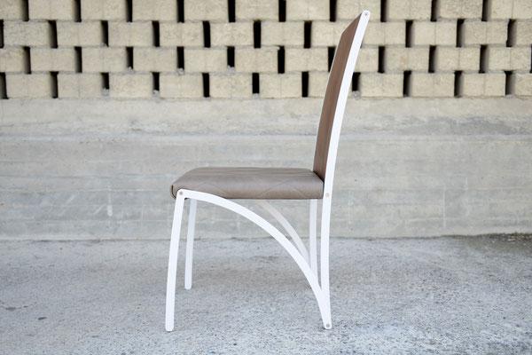 Seitenansicht von einem Stuhl mit einer Lehne aus Holz und einer Sitzfläche aus Leder, das Stuhl-Gestell ist weiss lackiert