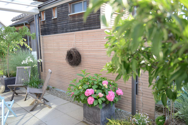 Sichtschutz-Wand aus Holz mit zwei Gartenstühlen auf einer Gartenterrasse