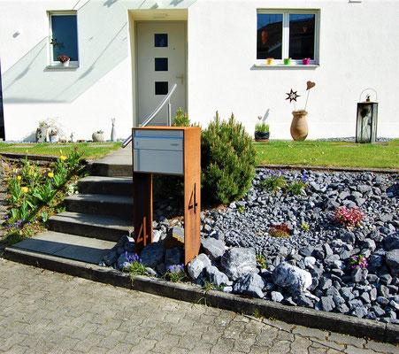 Briefkasten mit rostiger Optik vor einem Hauseingang