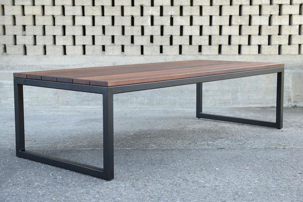 rechteckiger Gartentisch mit einem schwarzen Untergestell vor einer gemauerten Wand