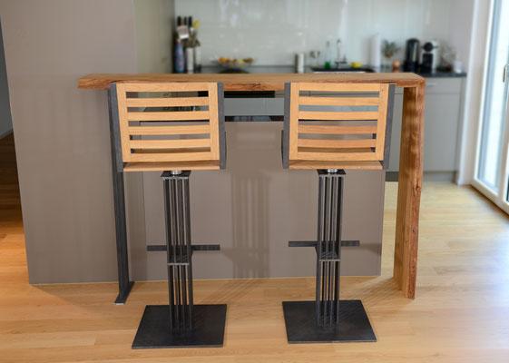 zwei Hochstühle aus Holz und Stahl von einer Theke aus Holz, im Hintergrund eine Küche