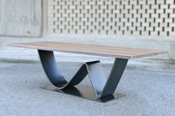 Großaufnahme von einem Tisch dessen Tischbein in eine W-Form gebogen ist