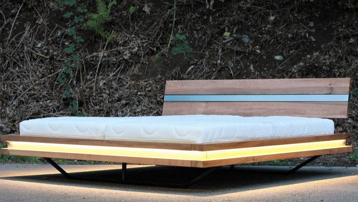 Bett aus Nussbaumholz vor einem bepflanztem  Hang