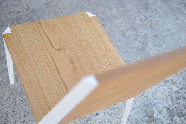 Vogelgesicht von einem Stuhl aus Holz vor einer gemauerten Wand