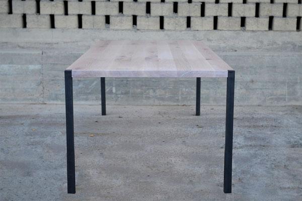 Seitenansicht von einem Tisch mit 4 Stahlbeinen vor einer gemauerten Wand