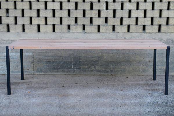 Tisch mit 4 Stahlbeinen vor einer gemauerten Wand