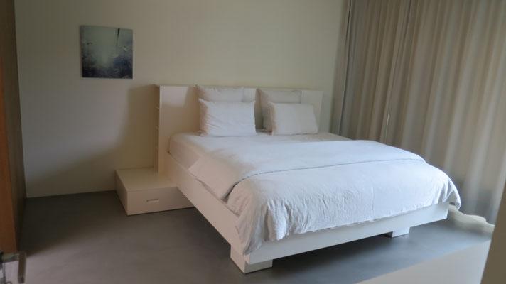 Bett weiss lackiert mit Schubladen unten, im Kopfteil seitliche Regale und mittig Truhe mit Deckel