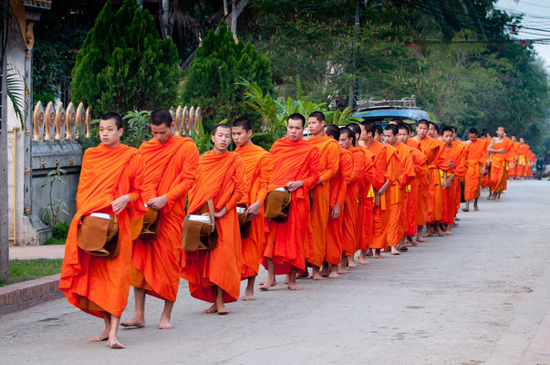The idea of the alms giving is for the Buddhist monks to make merit and also to collect food for their one meal of a day.