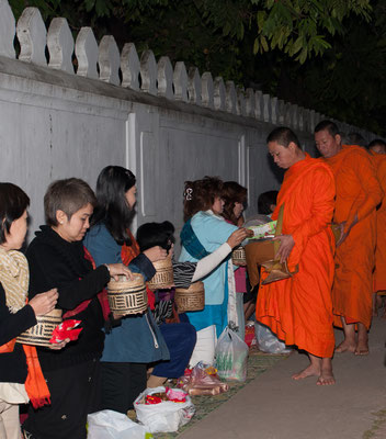 Follow the guidance of the locals by kneeling down ready to give your offering to the monks; most common gifts include rice, fresh fruit and traditional sweet snacks.