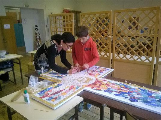 Valérie Manaud guidant un élève pour le collage des tesselles