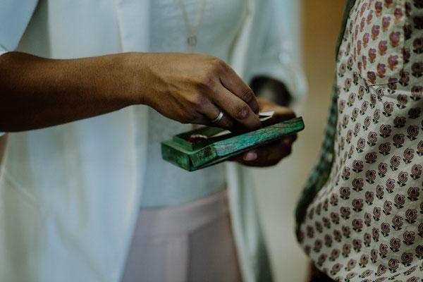 Nahaufname der Brauthände mit einem Geschenk