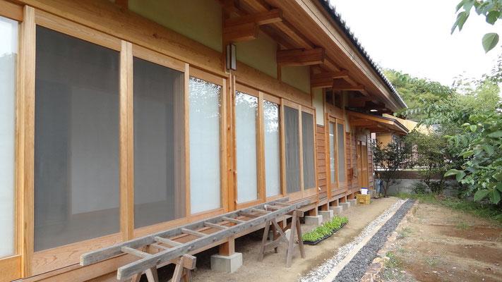 南外部の深い軒の出と木製建具。雨樋はなく雨落ちとした。