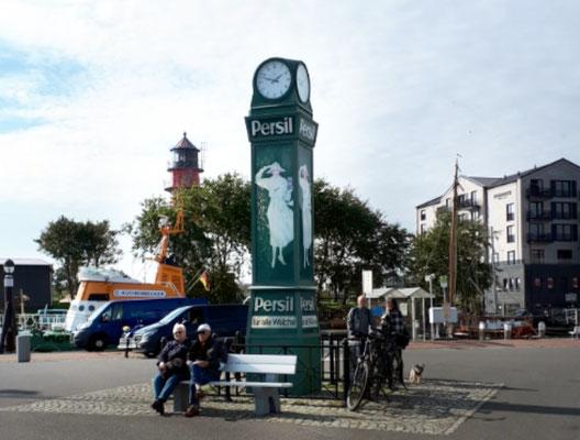 alte Werbesäule und dahinter der Leuchtturm