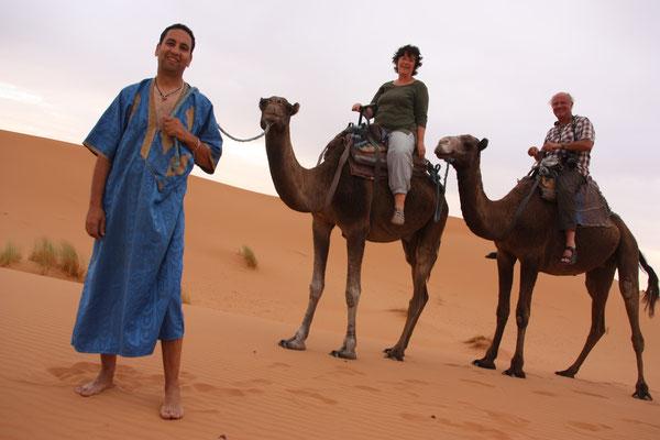 Hoch auf dem Dromedar geht es zum Sonnenuntergang in die Wüste