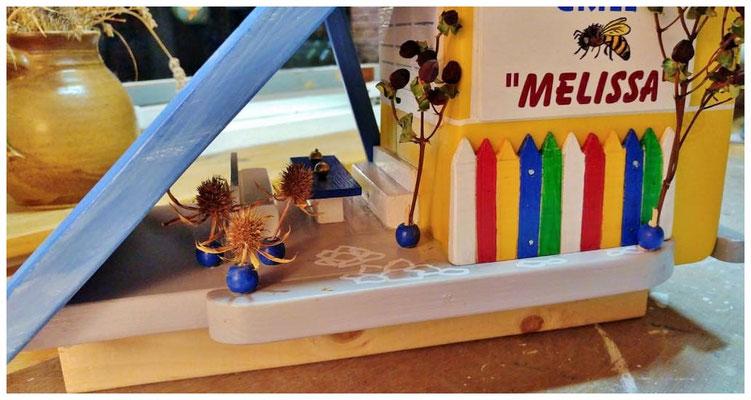 Vogelhuisje Melissa, geel huis met blauw dak, Restaurant Grill Melissa, buiten terras detail