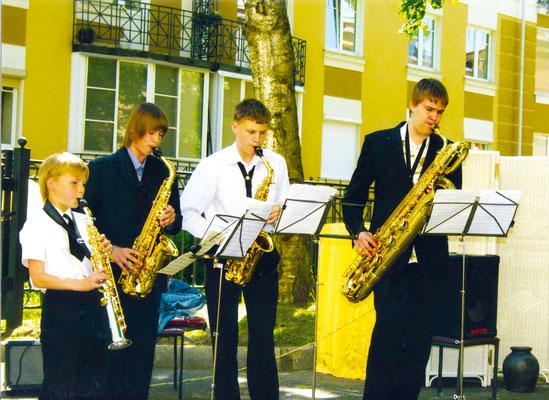 Ансамбль саксофонистов музыкальной школы выступает на традицион- ном концерте в школьном дворе, посвященном Дню защиты детей