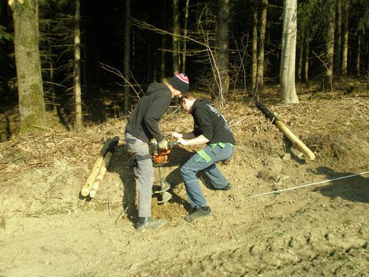 Die Holzpfähle mit  Erdbohrer und Kieß versetzen.
