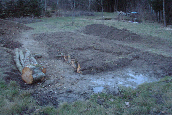 Die abgestochenen Rasensoden (Rasenziegel) kommen auf das Holz verkehrt herum drauf.