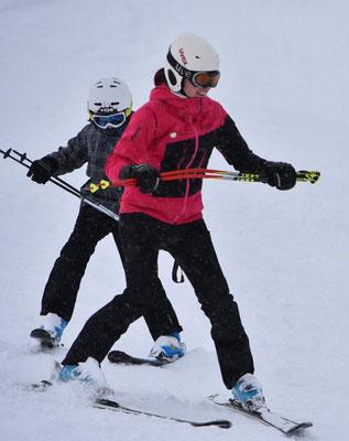Skilehrer zeigt Übungen beim Skikurs