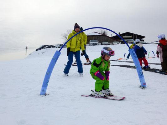 Kind fährt beim Zwergerl-Skikurs Skiteam Heufeld durch den Zauberbogen