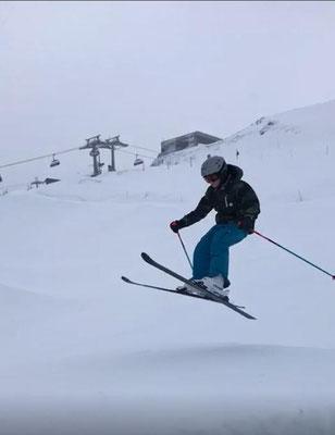 Skifahrer springt über Sprungschanze im Funpark.