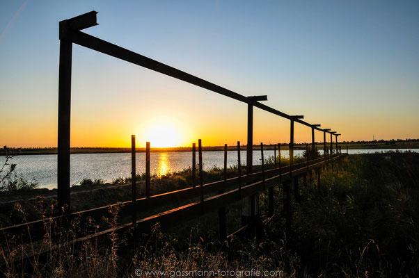 Sonnenuntergang und die verlassene Stahlkonstruktion am See