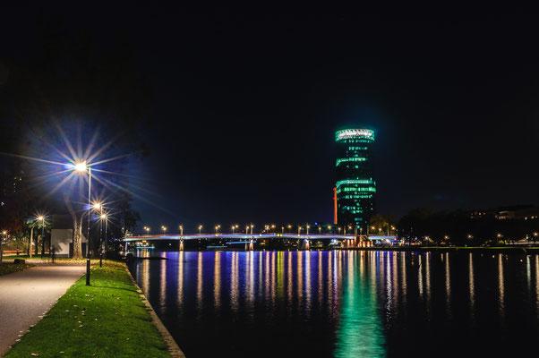 Nächtlicher traumhafter Blick auf die nächtliche Friedensbrücke und en Westhafen-Tower der einem Apfelwein-Glas ähnlich sieht