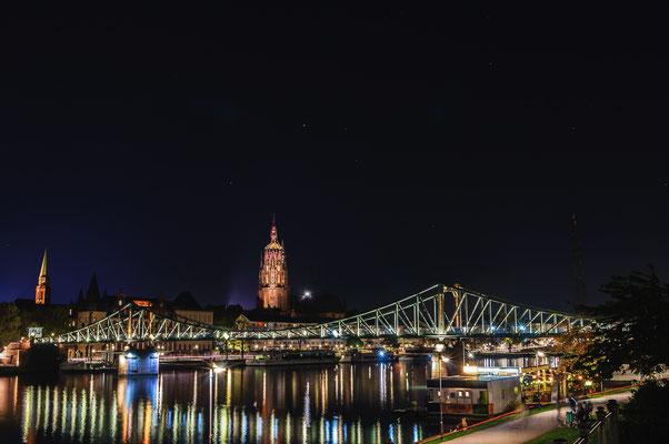 Nächtlicher Blick auf die Sehenswürdigkeit und bekannteste Brücke Eiserner Steg und den Dom von Frankfurt am Main