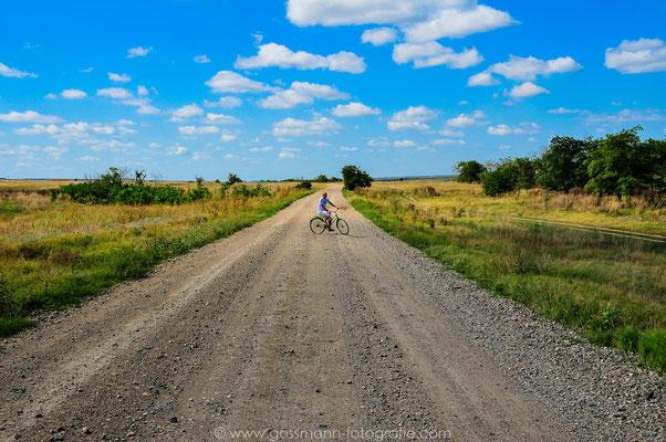 Steinige Feld-Straße ins ungewisse Seltener Anblick wenn sich die Straße mit dem Horizont verbindet