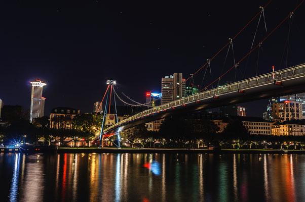 Nachtogfoto der  Holbeinsteg Hängebrücke für Fußgänger über den Fluss Main in Frankfurt mit Blick auf das Gebäude der Volksbank