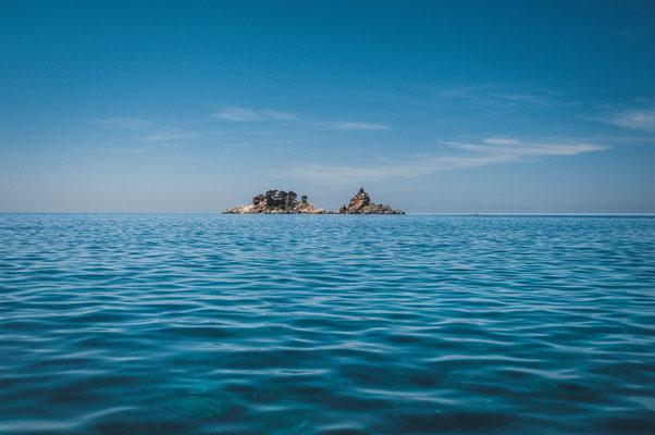 Kleine Insel mit einer Kapelle gegenüber vom Strand Petrovac in Montenegro