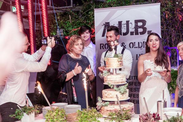 Das Anschneiden der Hochzeitstorte von der Braut und dem Bräutigam