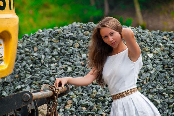 Junge Frau auf einer Baustelle Hübsche Frauen und Baustellenfahrzeuge Technik und wunderschöne Frauen