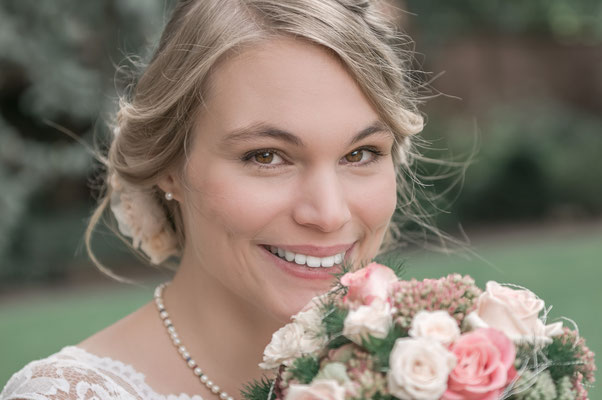Fröhliche Braut mit dem Hochzeitsstrauß