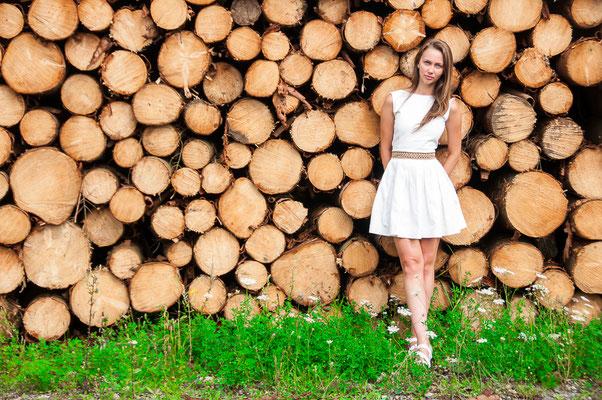 Junge hübsche Frau mit Hintergrund zu den Baumstämmen Forstwirtschaft Lifestyle Fotografie