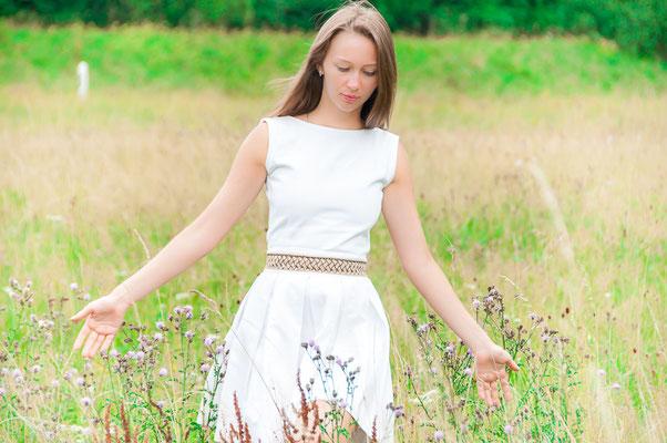 Wunderschöne junge russische Frau auf einer mit hochem Gras bewachsener Wiese Mein Dorfleben und die Nähe zur Natur