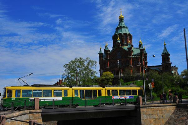 Blick auf die Brücke mit der vorbeifahrenden Straßenbahn und der Uspenski Kathedrale in Helsinki